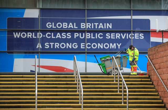 A man cleans the steps outside the Conservative Party Conference at the Manchester Central Convention Complex