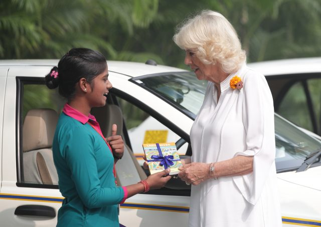 Camilla is presented with the book Lady Driver by taxi driver Poonam from Women on Wheels