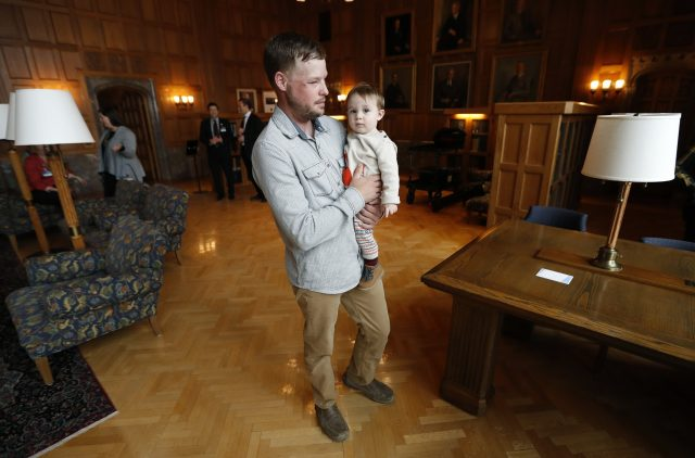 Andy Sandness holds 17-month-old Leonard Ross (Charlie Neibergall/AP)