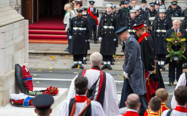 The Duke of Cambridge,  left, and Prince Harry, watched by Foreign Secretary Boris Johnson, bow their heads in respect after laying wreaths