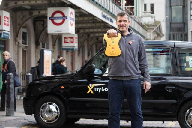 London black cab driver John Hamilton holds a defibrillator  (PA)