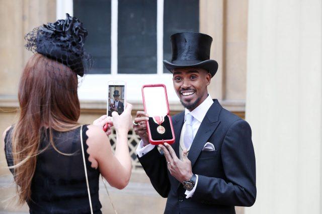 Sir Mo's wife Tania takes his photo outside Buckingham Palace (Jonathan Brady/PA)