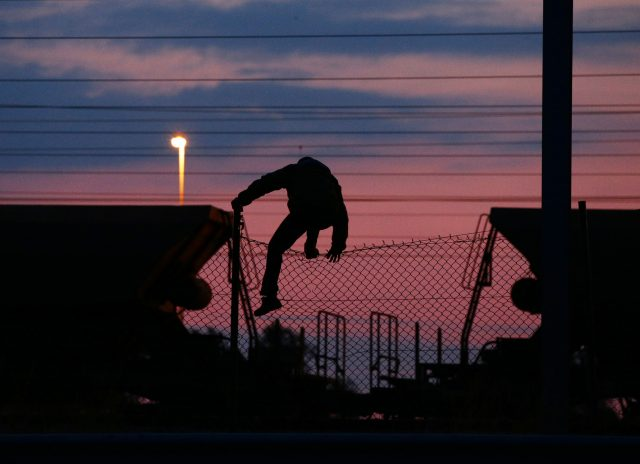 A migrant climbs over a fence on to the tracks at the Eurotunnel site at Coquelles in Calais