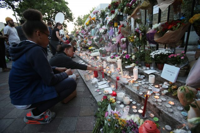 People lay flowers and tributes outside Notting Hill Methodist Church, close to Grenfell Tower in west London