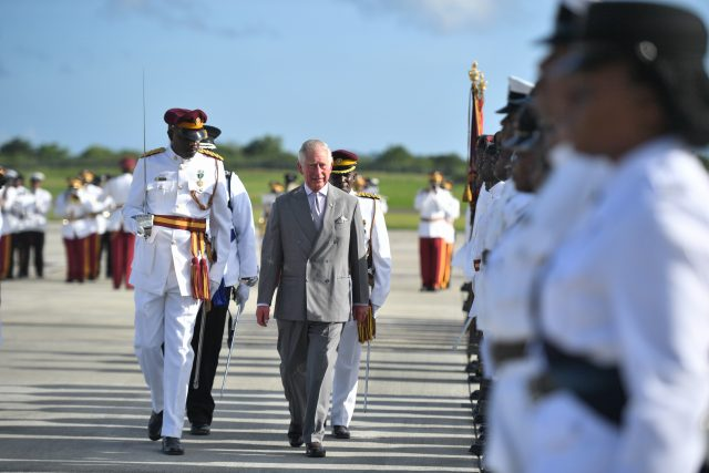 The Prince of Wales inspects a Guard of Honour as he arrives at VC Bird International Airport in Antigua