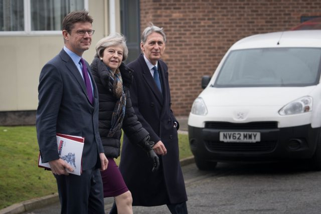 Prime Minister Theresa May walks with Business Secretary Greg Clark and Chancellor Philip Hammond