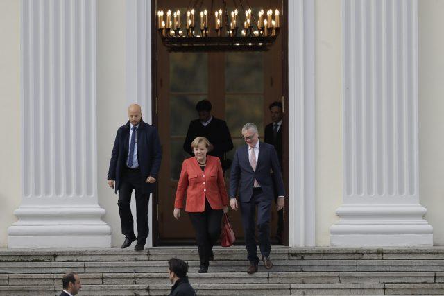 German Chancellor Angela Merkel, centre, leaves Bellevue Palace after a meeting with German President Frank-Walter Steinmeier