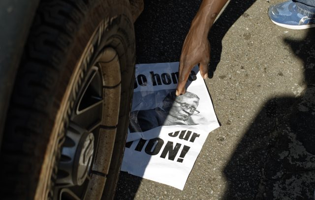 Posters of Robert Mugabe are placed under the wheels of passing vehicles