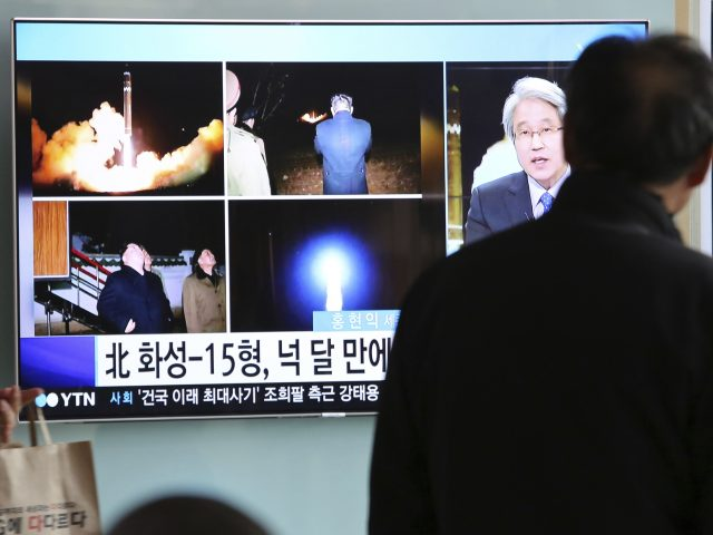 Commuters watch news reports on the latest launch in Seoul