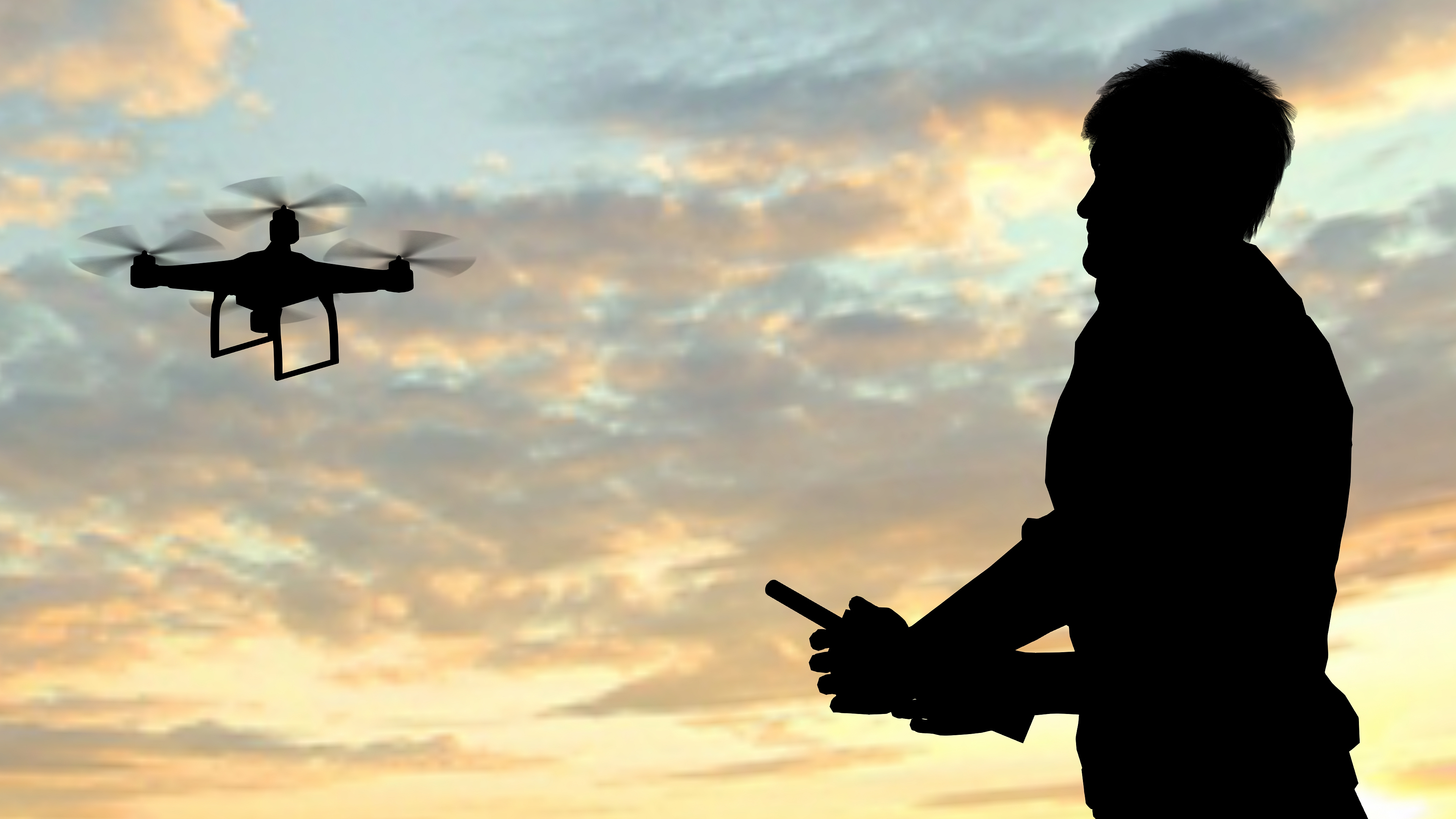 man operating of flying drone quadrocopter at sunset (Bestgreenscreen/Getty Images)
