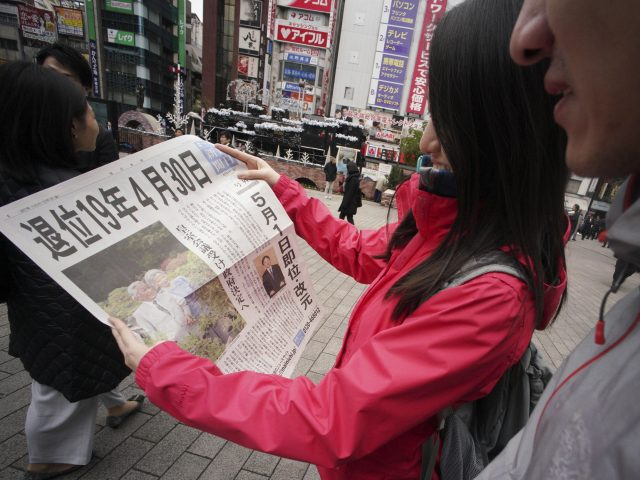 Passers-by read the news in Tokyo