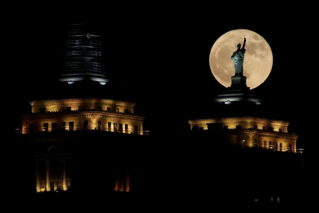 A supermoon rises in front of a replica of the Statue of Liberty sitting atop the Liberty Building in Buffalo, New York state (Julio Cortez/AP)