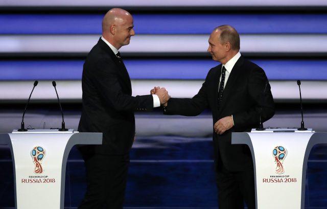 Vladimir Putin and Gianni Infantino shake hands