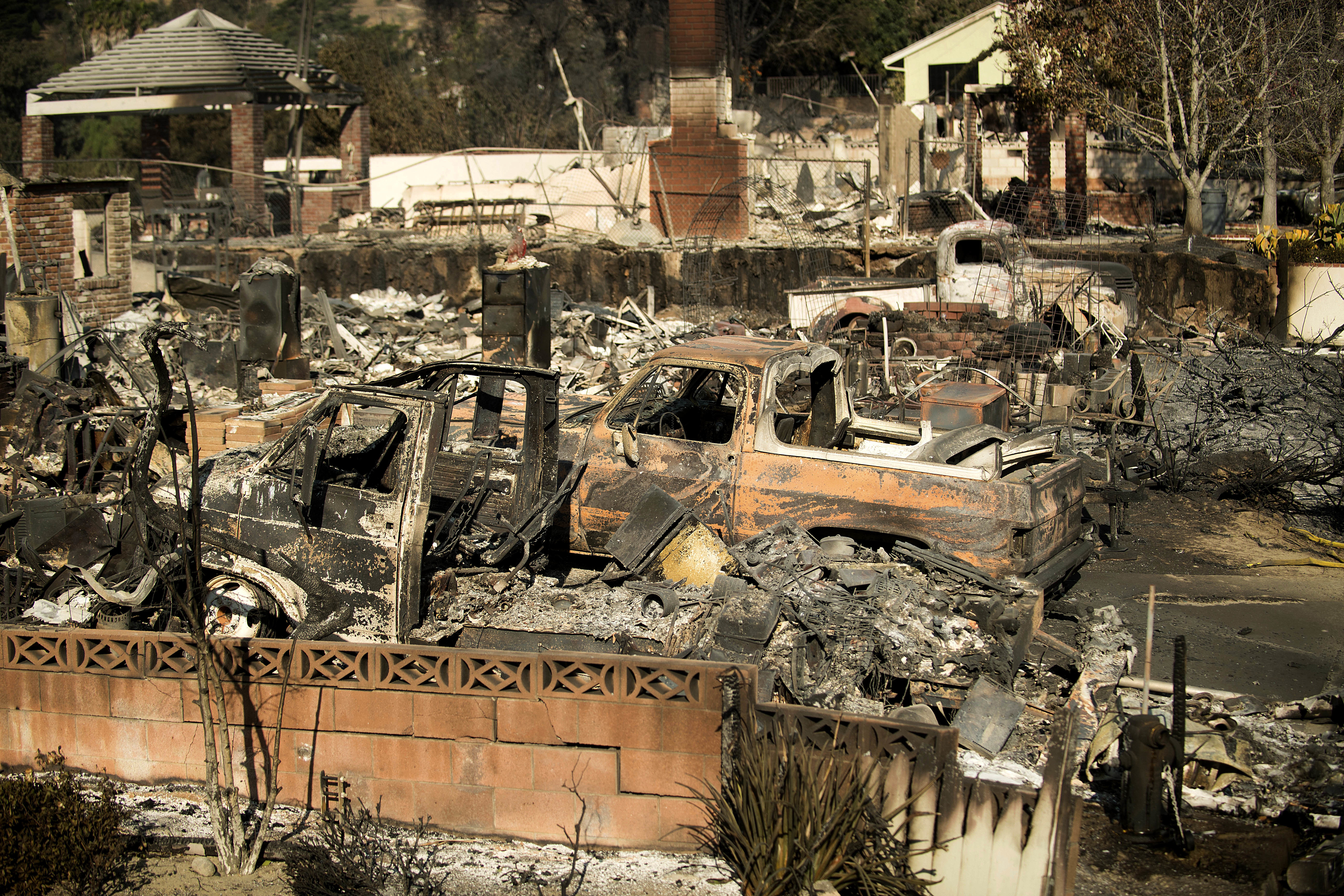 Rubble and burned vehicles line properties scorched by a wildfire  (Noah Berger/AP)