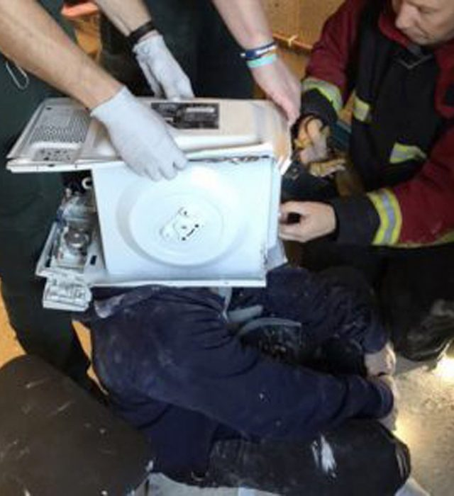 Firefighters working to release a YouTube prankster who cemented his head inside a microwave (West Midlands Fire Service/PA)