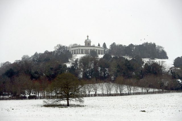 The Dashwood Mausoleum stands from the snow covered hills near West Wycombe, Buckinghamshire (Steve Parsons/PA)