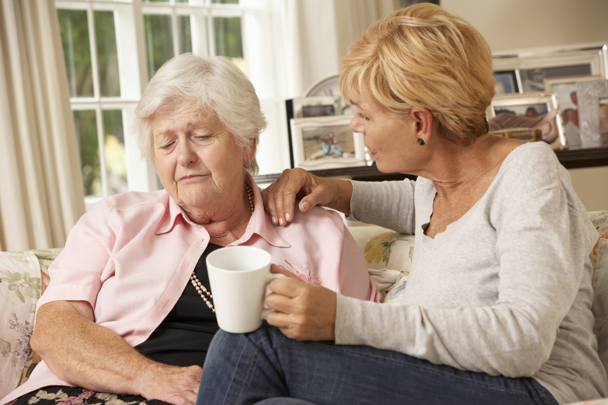 Unhappy elderly woman and her daughter chatting on sofa (Thinkstock/PA)