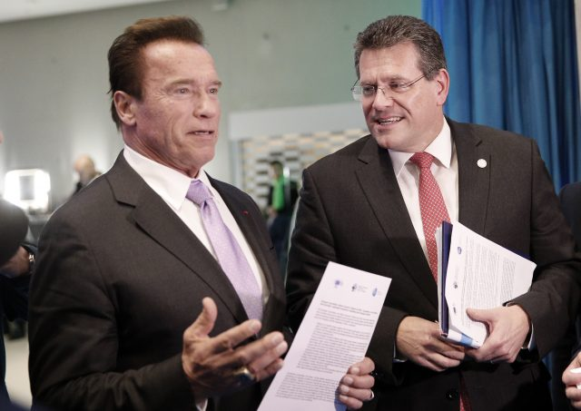 Arnold Schwarzenegger, left, speaks with European Commissioner for Energy Union Maros Sefcovic at the One Planet Summit (Christophe Ena/AP)