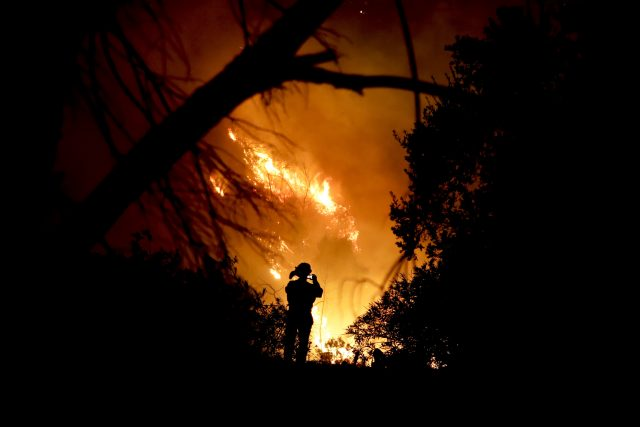 A firefighter takes a photo in Montecito (Chris Carlson/AP)
