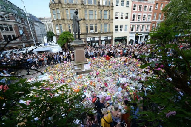 Crowds look at the floral tributes after a minute's silence in St Ann's Square, Manchester, to remember the victims of the terror attack at the Manchester Arena during an Ariana Grande gig (Ben Birchall/PA)