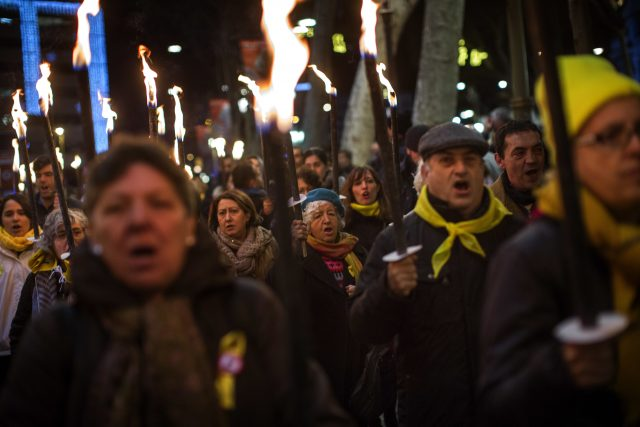 People march holding torches during a protest in support of Catalonian politicians who have been jailed (Emilio Morenatti/AP)