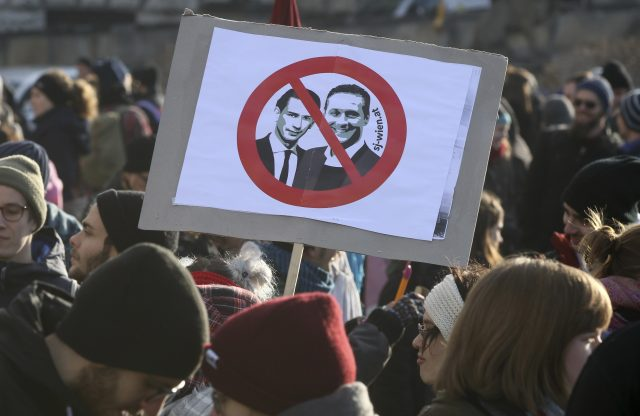 Protestors hold a poster with new Chancellor Sebastian Kern and new Vice Chancellor Heinz-Christian Strache (Ronald Zak/AP)