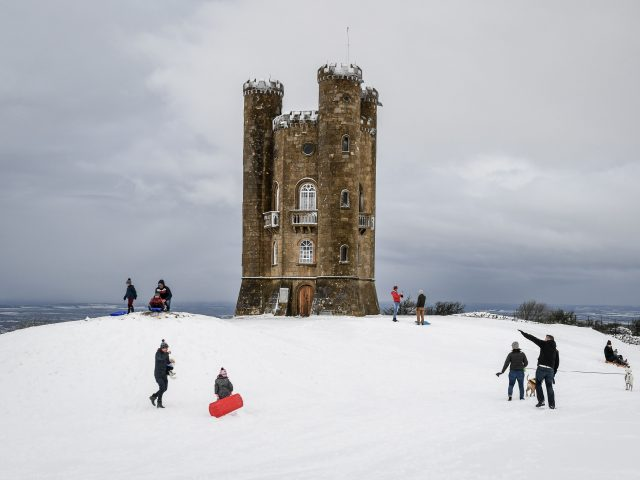 People enjoy the snow at Broadway Tower on the Cotswold hills, Worcestershire (PA)