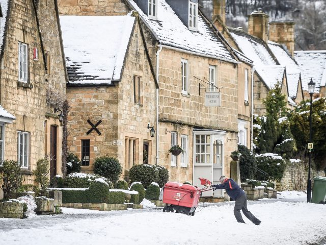 A postman pushes his trolley over snow on the High Street in Broadway, Worcestershire (PA)