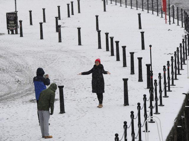 People take photos in the snow in York (John Giles/PA)