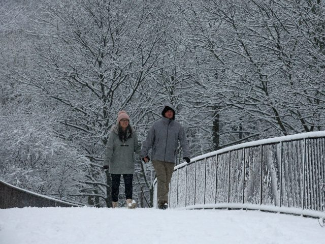 A couple walking through the snow in Glasgow (Andrew Milligan/PA)
