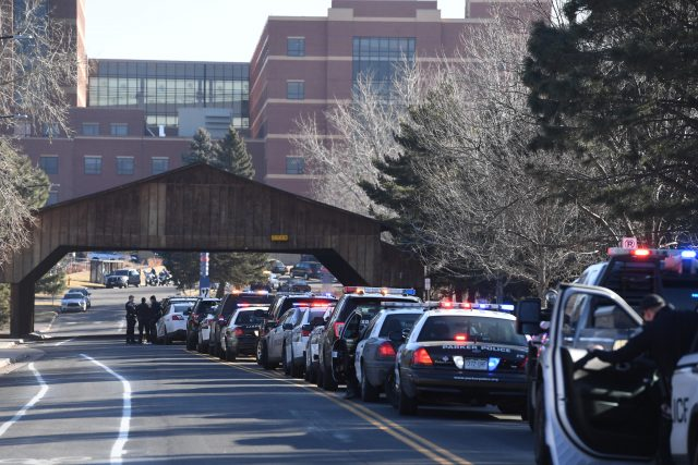 Police officers line up their patrol cars outside of Littleton Adventist Hospital for a procession honouring the officer who was fatally wounded (John Leyba/The Denver Post via AP)