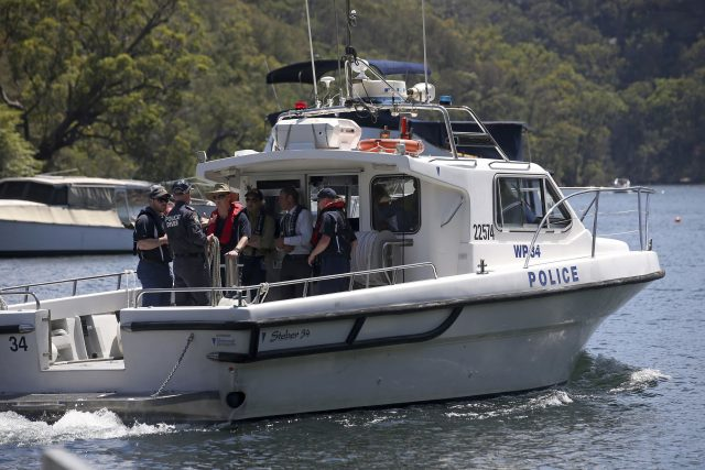 Police and and Australian Transport Safety Bureau investigators depart on a police boat to go to the scene (Rick Rycroft/AP)