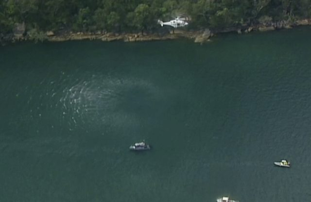 A search and rescue helicopter flies above search boats in Hawkesbury River (Australian Media via Pool/PA)