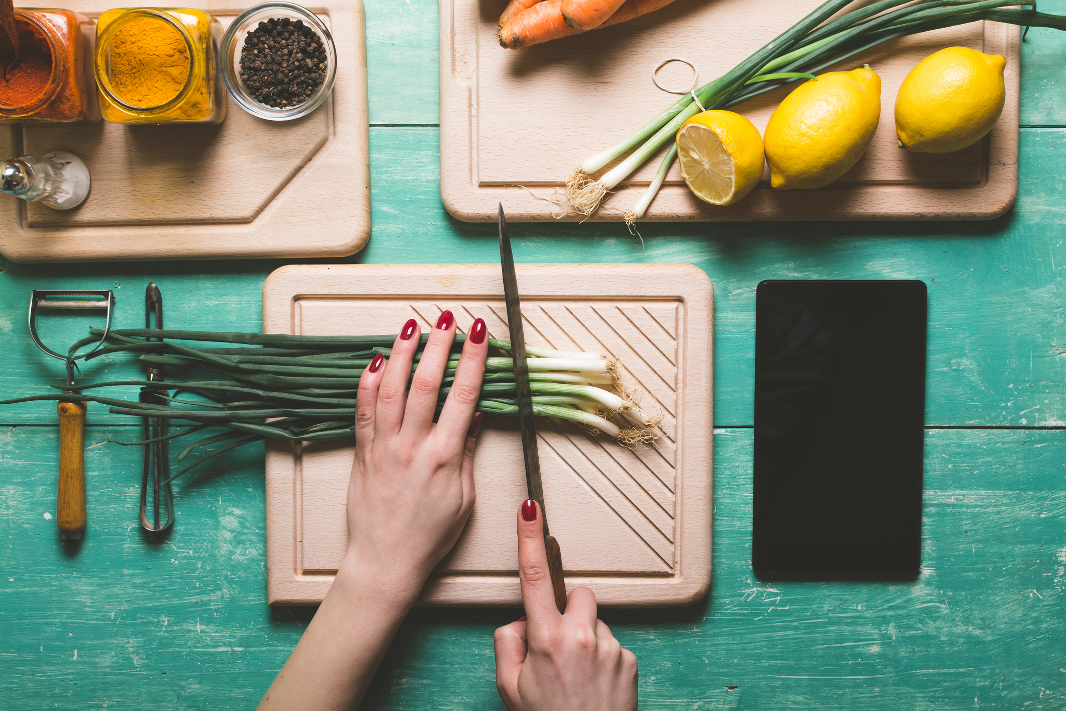 Generic image showing woman's hands cutting fresh spring onion on a blue wooden table (Thinkstock/PA)