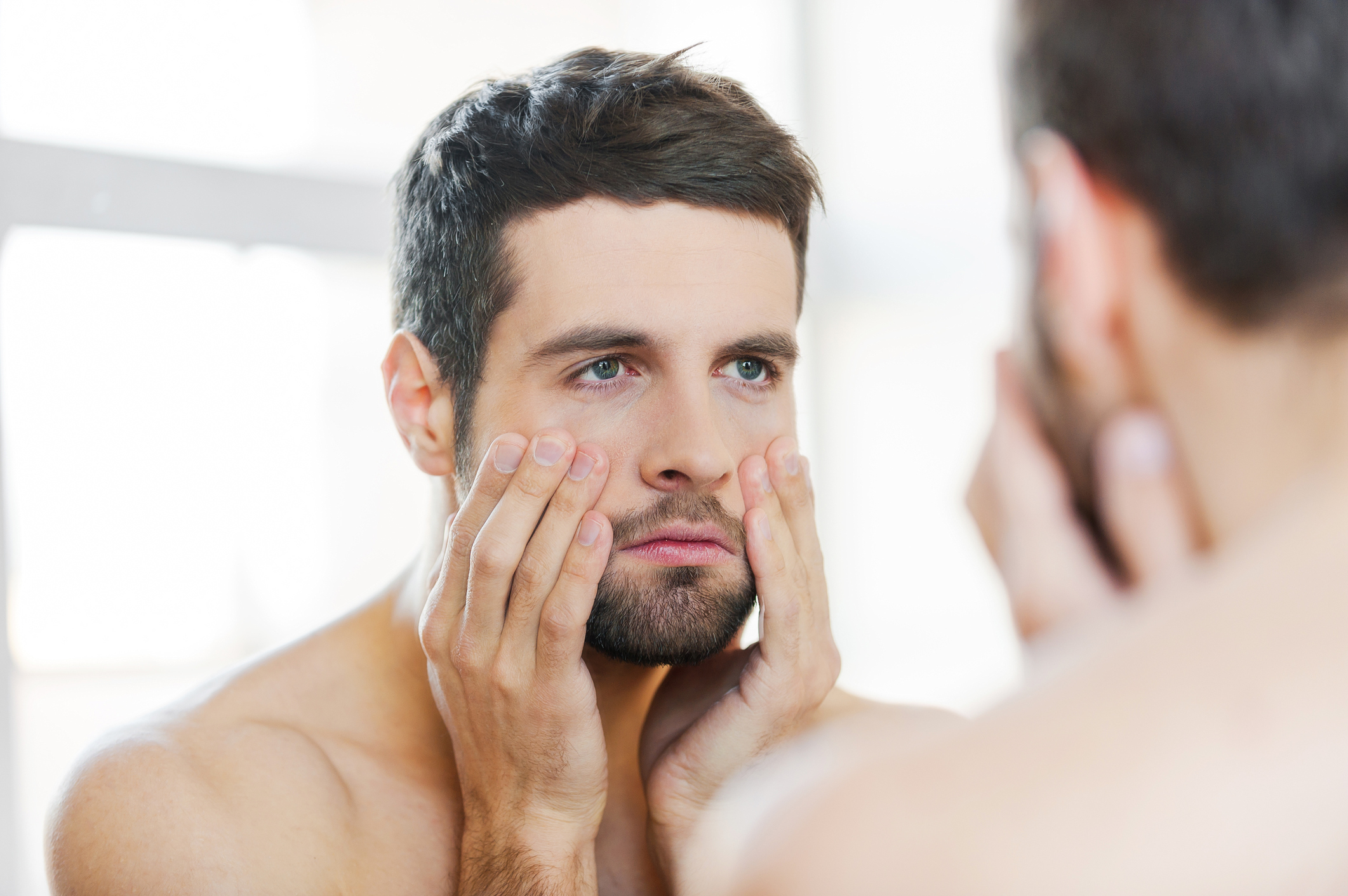 Frustrated young man touching his face and looking at himself while standing against a mirror