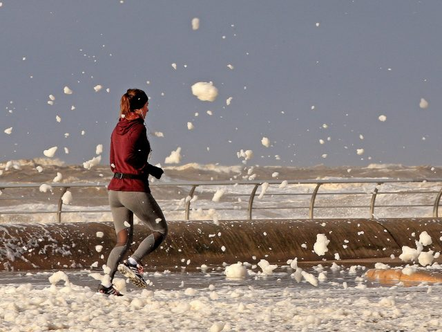 A woman jogs through sea foam in Blackpool