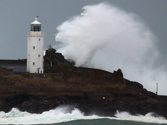 Waves crash against Godrevy Lighthouse on Godrevy Island in St Ives Bay, Cornwall