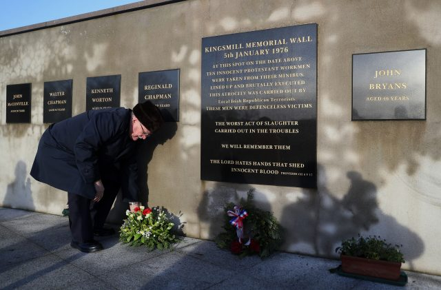 A man lays a wreath at the Kingsmill memorial  in South Armagh (PA)