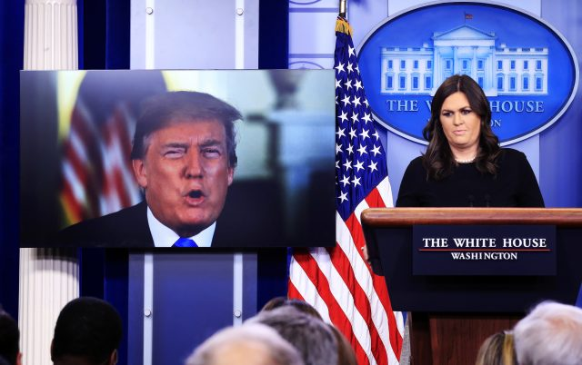 Mr Trump speaks via a video monitor to journalists in a daily press briefing with Sarah Huckabee Sanders