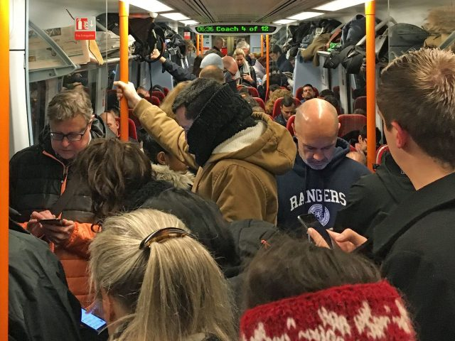Commuters ride a crowded South Western Railway train on the Portsmouth to London Waterloo line