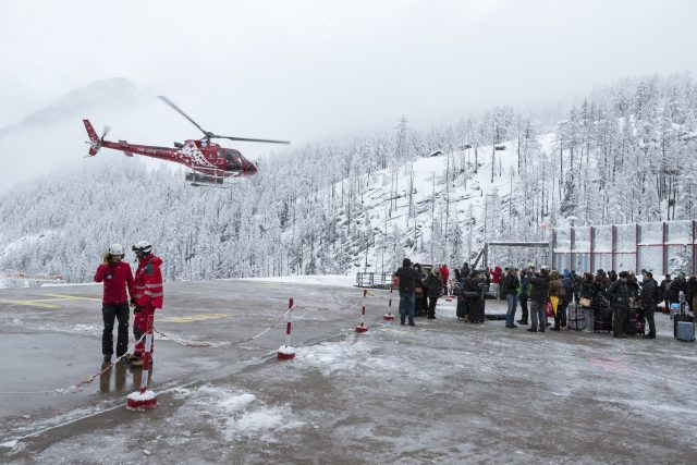 Tourists wait in line at the heliport of Air Zermatt for a flight by airlift into the valley to Raron, in Zermatt (Dominic Steinmann/Keystone via AP)