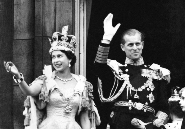 The Queen and the Duke of Edinburgh wave from the balcony to the onlooking crowds around the gates of Buckingham Palace after the coronation (PA)