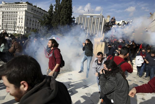 Protesters try to avoid tear gas fired by police (Thanassis Stavrakis/AP)