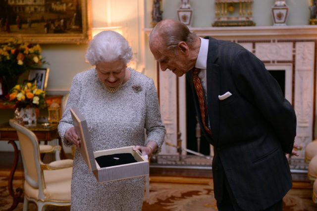 The Queen, with the Duke of Edinburgh, examining a gift (PA)