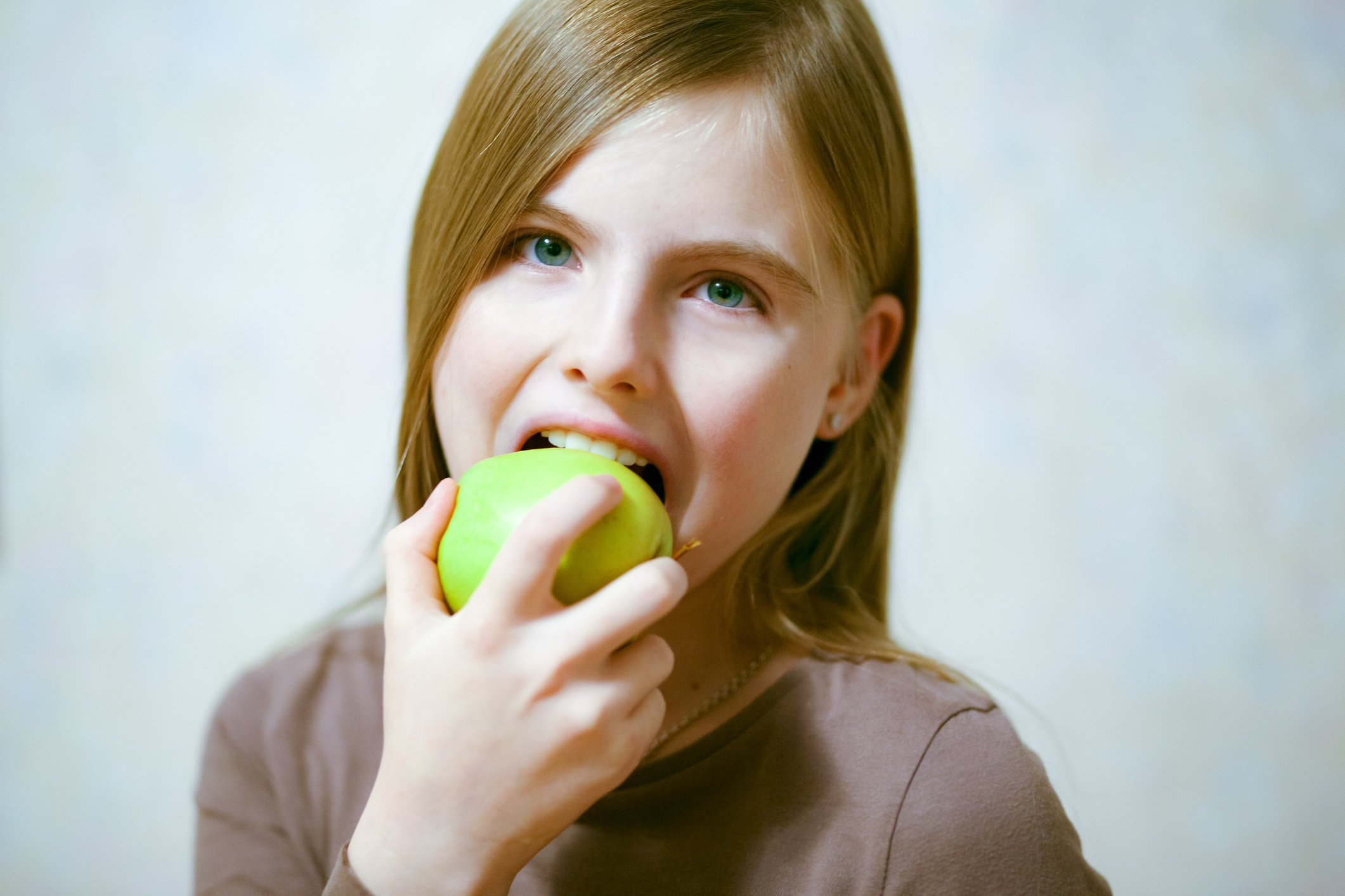 Young girl eating a green apple (Thinkstock/PA)