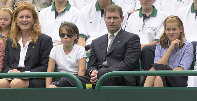The Duke and Duchess of York sit with Beatrice (left) and Eugenie (right) in the grounds of Buckingham Palace at a charity tennis event in July 2000 (Fiona Hanson/PA)