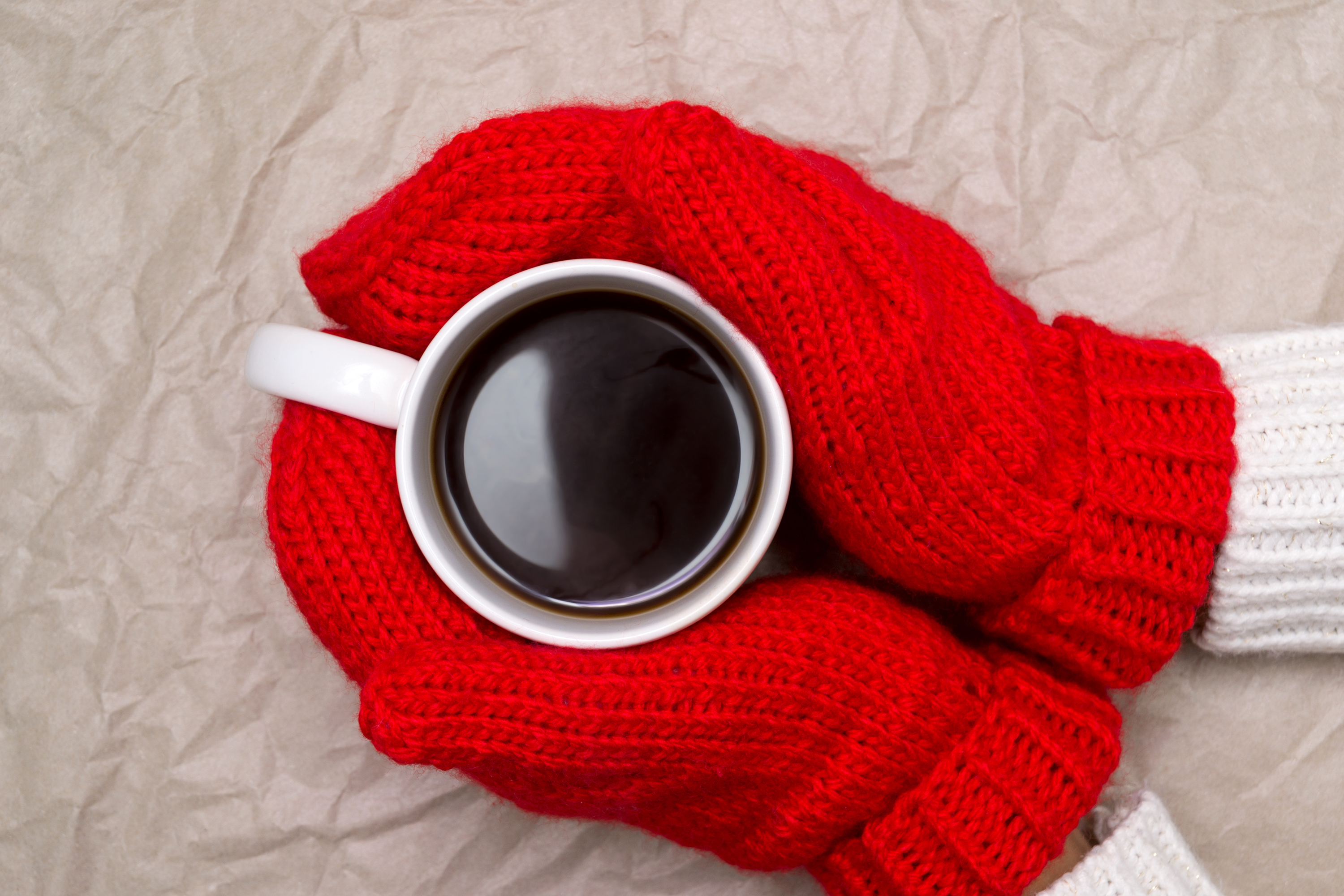 Woman in red knitted mittens and cup of coffee (Thinkstock/PA)
