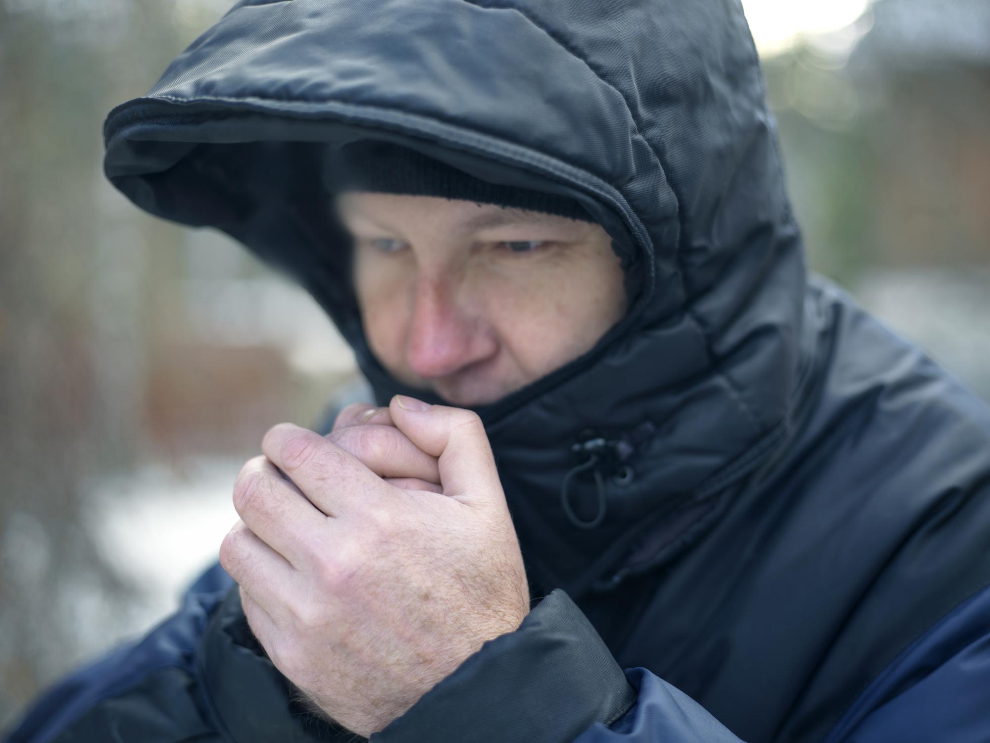 Man wearing hood warming his hands