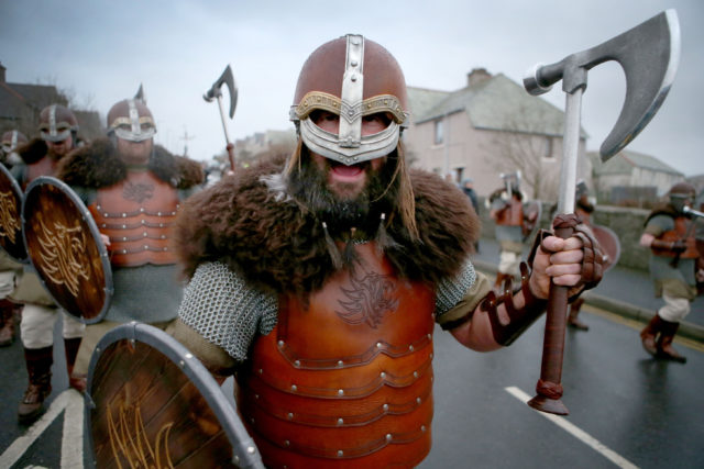 A member of the Jarl Squad dressed in a Viking suit on the parade through the street in Lerwick (Jane Barlow/PA)