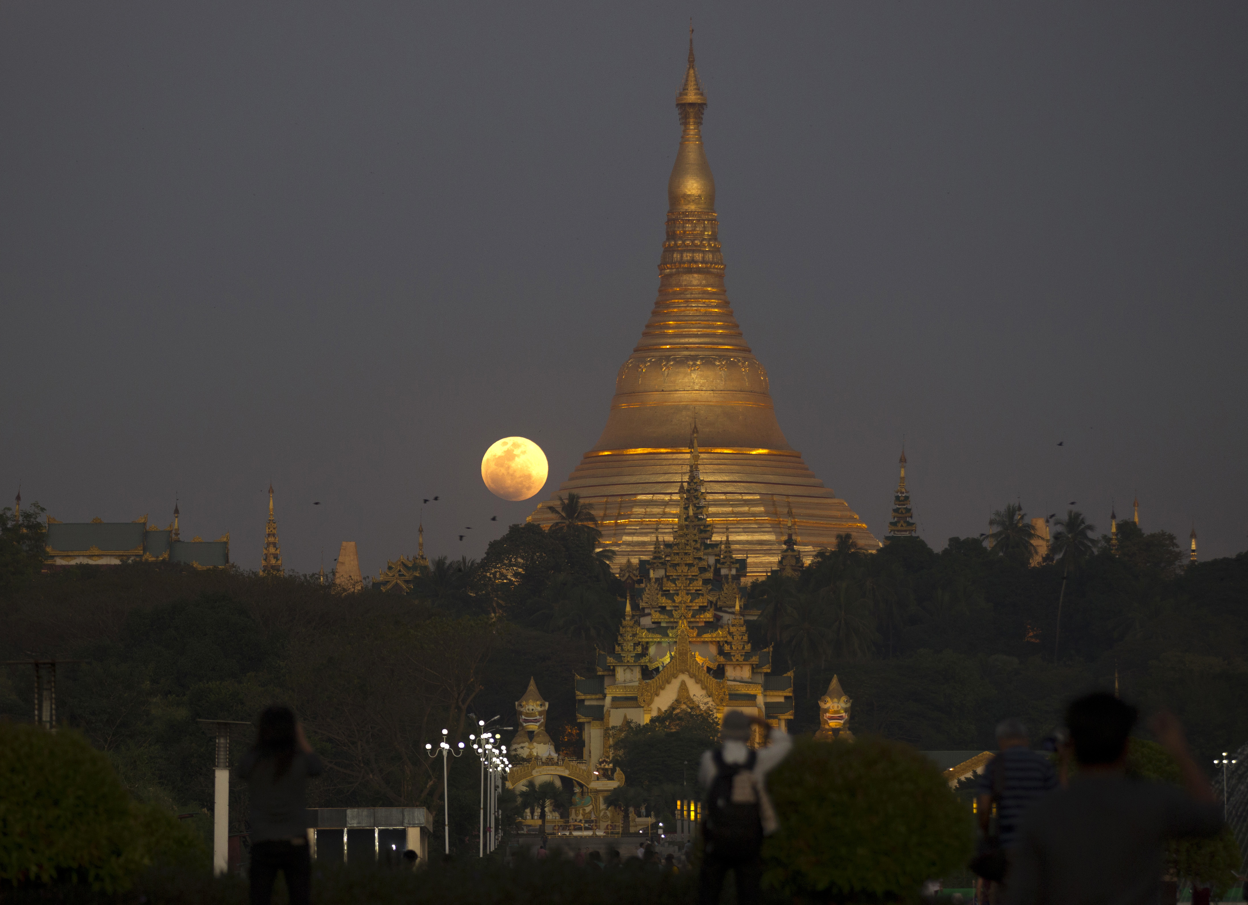 The moon rises behind Myanmar landmark Shwedagon pagoda